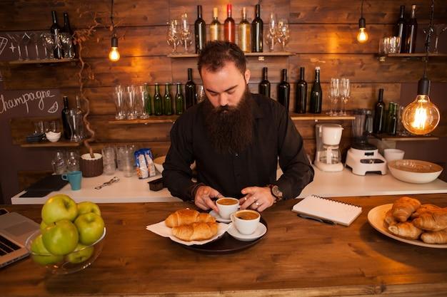 Serveur hipste perlé préparant le café derrière le comptoir du bar