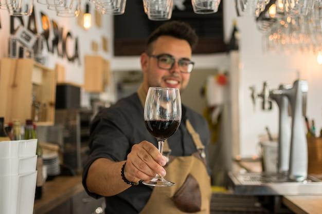 Serveur offrant une coupe de vin dans un pub
