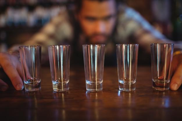 Serveur plaçant des verres à liqueur sur le comptoir