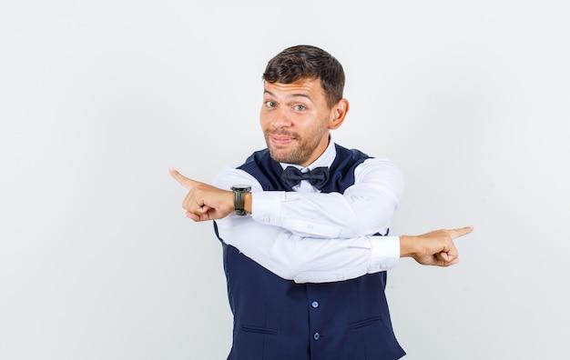 Serveur pointant les doigts sur le côté en chemise, gilet et drôle, vue de face.