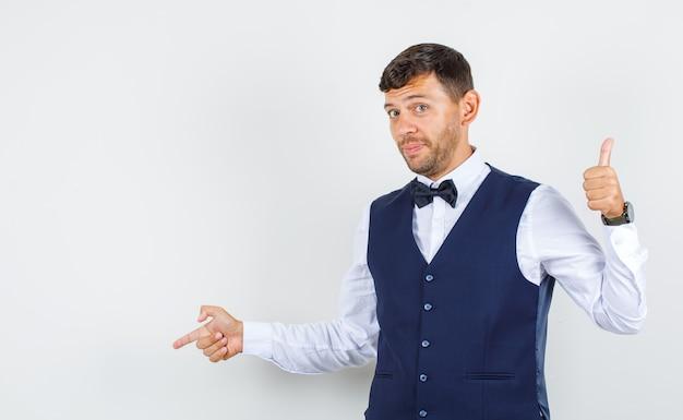 Serveur pointant vers le bas avec le pouce en chemise, gilet et à la douce. vue de face.