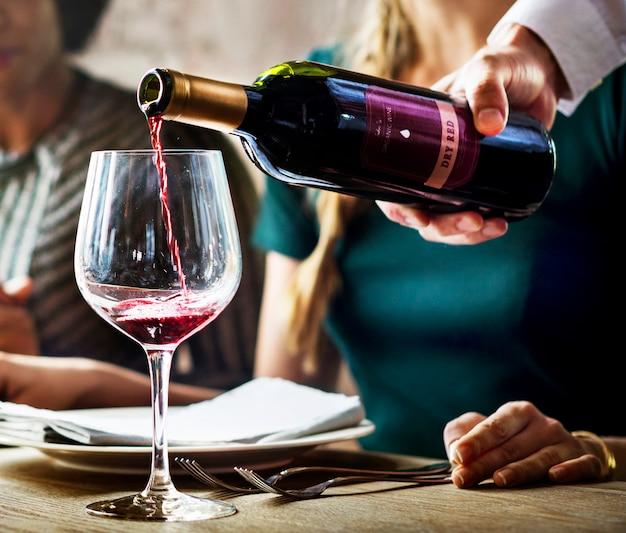Serveur poring servant du vin rouge aux clients dans un restaurant
