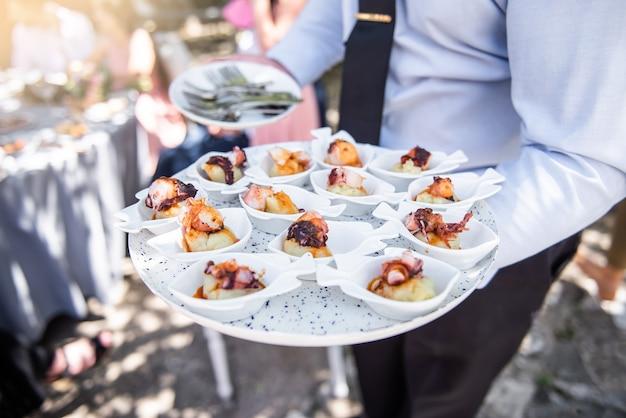 Serveur portant un plateau blanc plein de nourriture lors d'un événement pour les gens