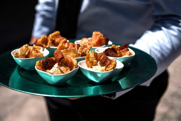 Serveur portant un plateau vert plein de nourriture lors d'un événement pour les gens