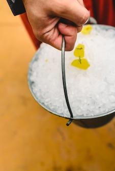 Serveur portant un seau en métal rempli de glace pour refroidir les boissons en été.