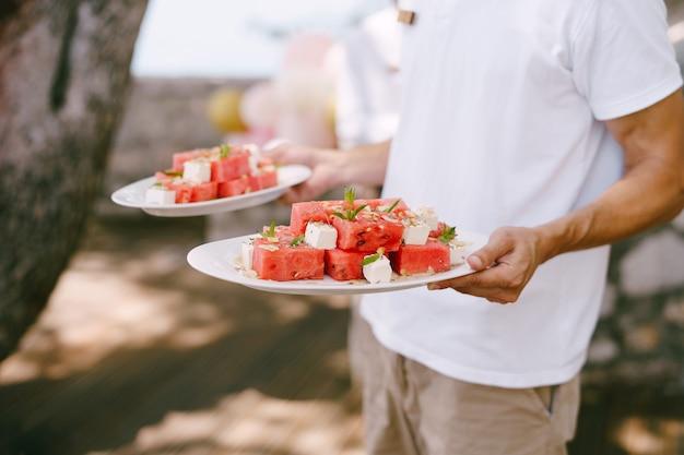 Le serveur porte des tranches de pastèque avec du fromage et des herbes sur les assiettes