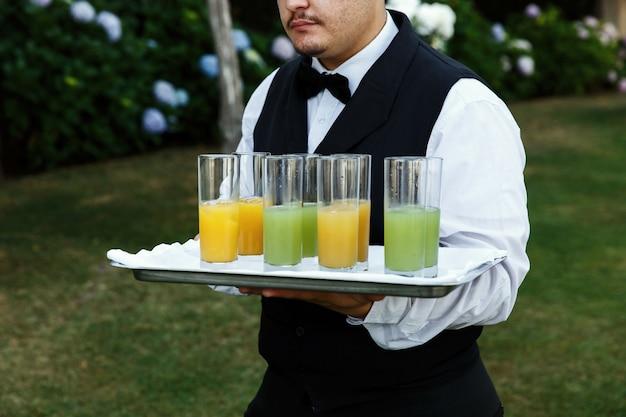 Serveur porte des verres avec du jus
