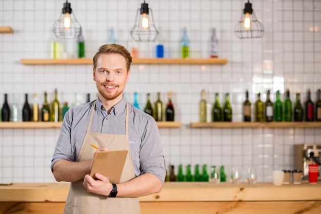 Serveur professionnel. ravi gentil bel homme debout devant le comptoir et vous regarde tout en travaillant dans le café