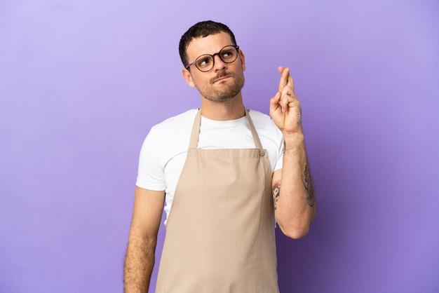 Serveur de restaurant brésilien sur fond violet isolé avec les doigts croisés et souhaitant le meilleur