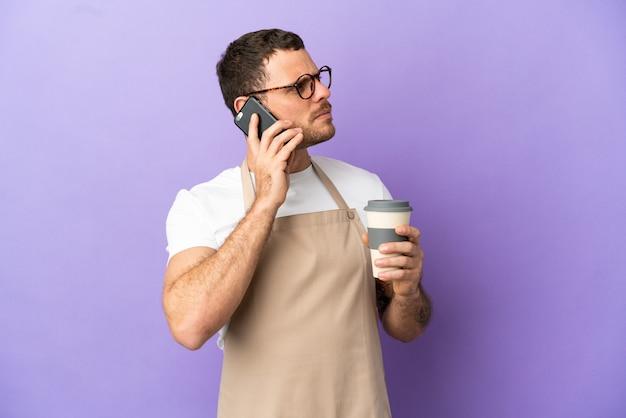 Serveur de restaurant brésilien sur fond violet isolé tenant du café à emporter et un mobile