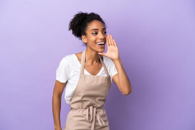 Serveur de restaurant femme latine isolée sur fond violet criant avec la bouche grande ouverte sur le côté