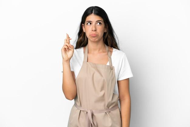 Serveur de restaurant sur fond blanc isolé avec les doigts croisés et souhaitant le meilleur