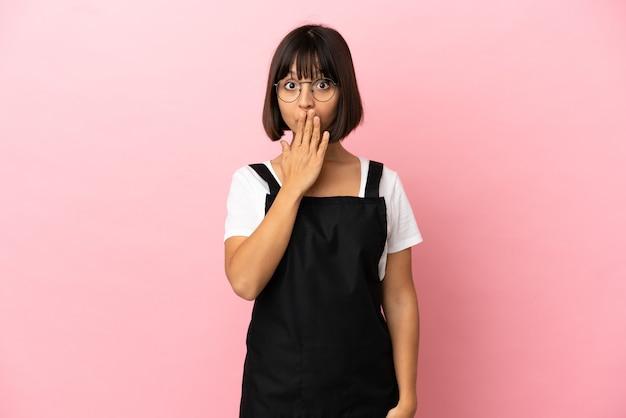 Serveur de restaurant sur fond rose isolé couvrant la bouche avec la main