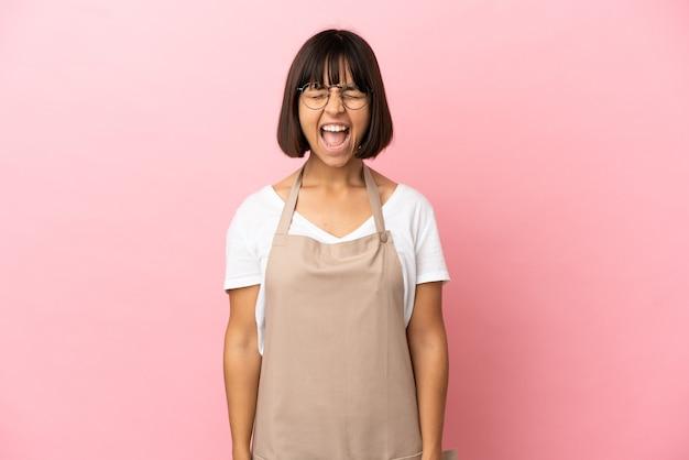 Serveur de restaurant sur fond rose isolé criant à l'avant avec la bouche grande ouverte