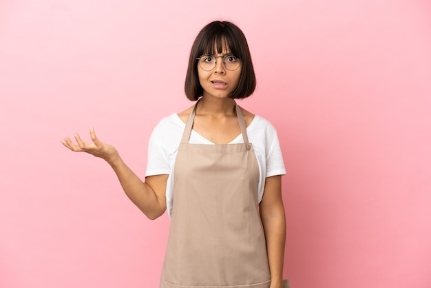 Serveur de restaurant sur fond rose isolé faisant des doutes geste