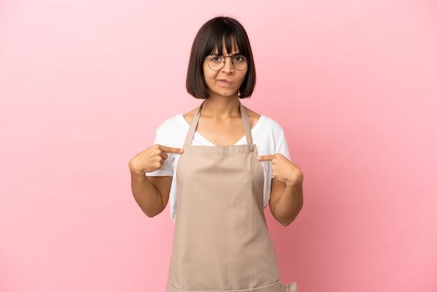 Serveur de restaurant sur fond rose isolé pointant sur soi