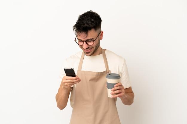 Serveur de restaurant homme caucasien isolé sur fond blanc tenant du café à emporter et un mobile