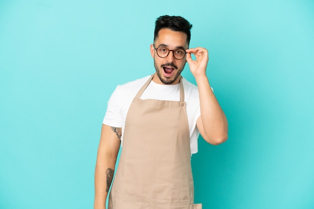Serveur de restaurant homme caucasien isolé sur fond bleu avec des lunettes et surpris