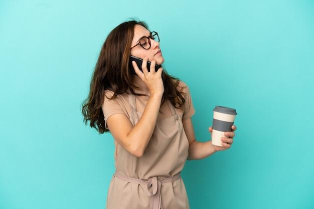 Serveur de restaurant tenant du café à emporter et un mobile