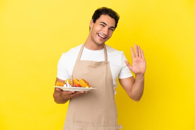 Serveur de restaurant tenant des gaufres sur fond jaune isolé saluant avec la main avec une expression heureuse