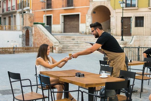 Un serveur sert un café à une jeune femme sur une terrasse de pub