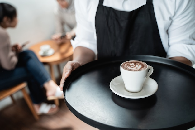 Serveur sert une tasse de café sur le plateau