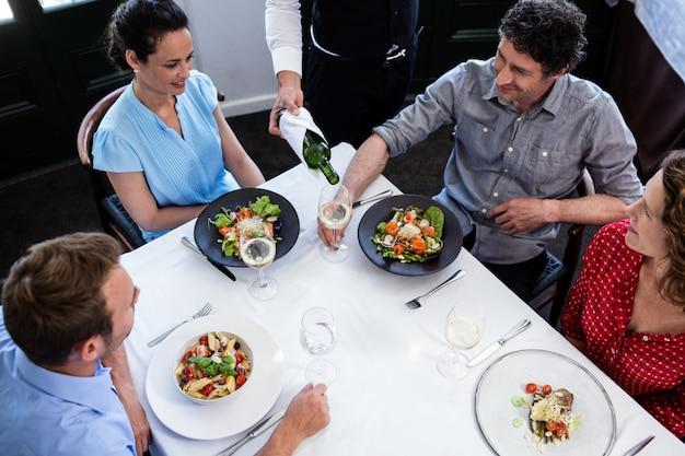 Serveur servant du vin à un groupe d'amis tout en déjeunant