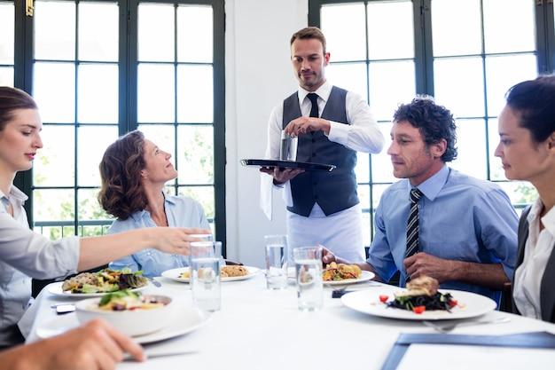 Serveur servant de l'eau à des hommes d'affaires