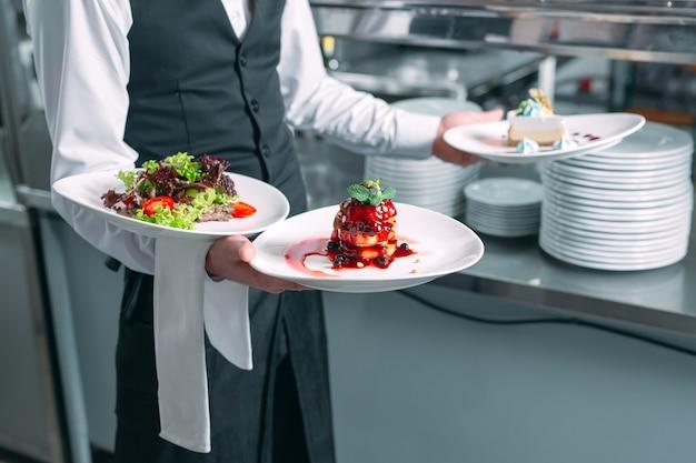 Serveur servant en mouvement en service au restaurant. le serveur porte de la vaisselle.