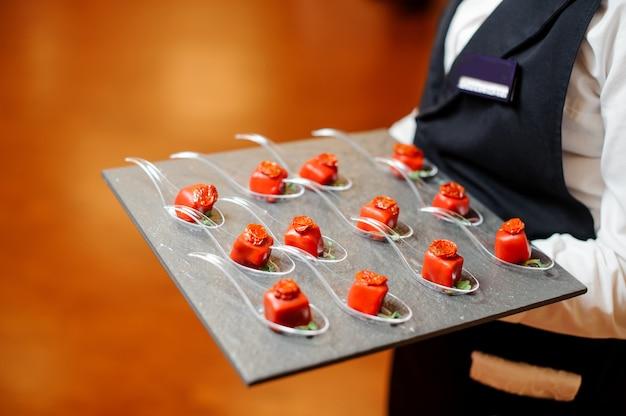 Serveur servant un pâté de petites entrées salées dans un glaçage rouge décoré de tomates séchées et de micro-feuilles