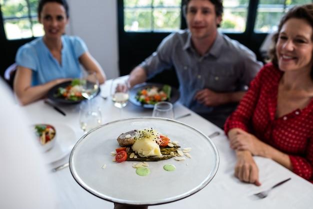 Serveur servant un repas à un groupe d'amis
