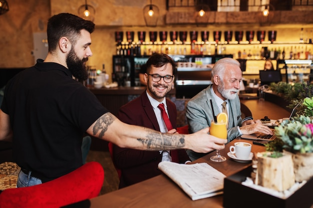 Serveur servant un verre aux gens d'affaires au restaurant
