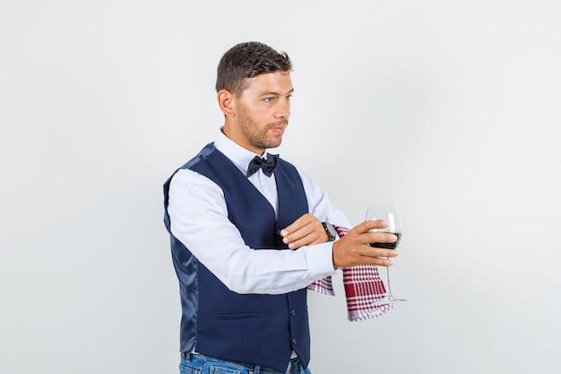 Serveur servant un verre de boisson en chemise, gilet, jeans et à la vue de face, occupé.