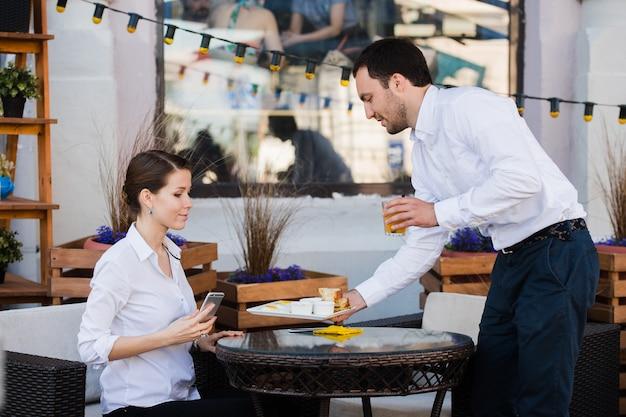 Serveur serveur à la table de travail liste de promotions du menu de lecture pour un groupe de personnes