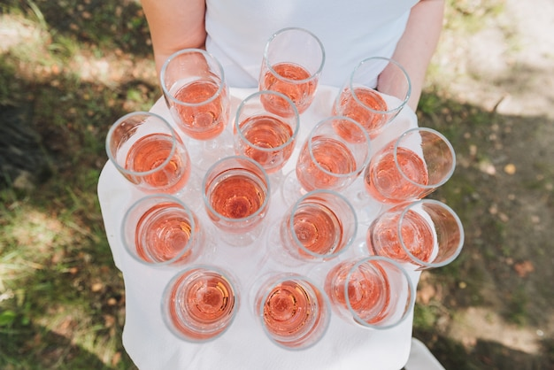 Serveur ou serveur tenant un plateau de verres de vin mousseux rose pour les invités lors d'une réception de mariage