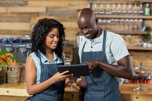 Serveur souriant et serveuse à l'aide de tablette numérique au comptoir