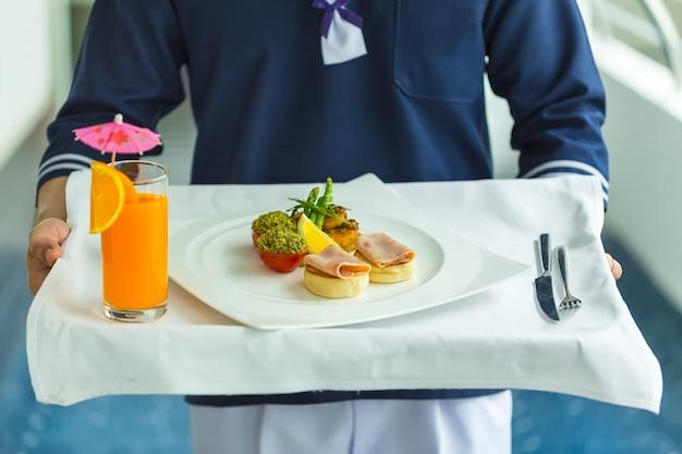 Serveur tenant l'assiette avec petit-déjeuner devant la chambre d'hôtel. serveur, uniforme, marin, sai