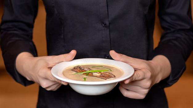Serveur tenant une belle soupe aux champignons