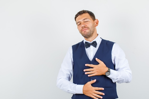 Serveur tenant les mains sur la poitrine et le ventre en chemise, gilet et à la vue détendue, de face.
