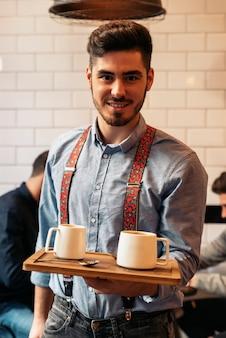Serveur tenant un plateau avec des cafés dans le bar.