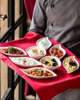 Serveur tient un plateau avec des plats d'accompagnement en meze turc