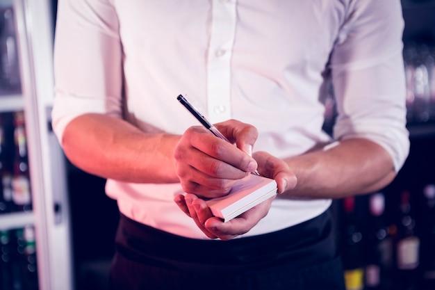 Serveur en train d'écrire une commande dans un bar