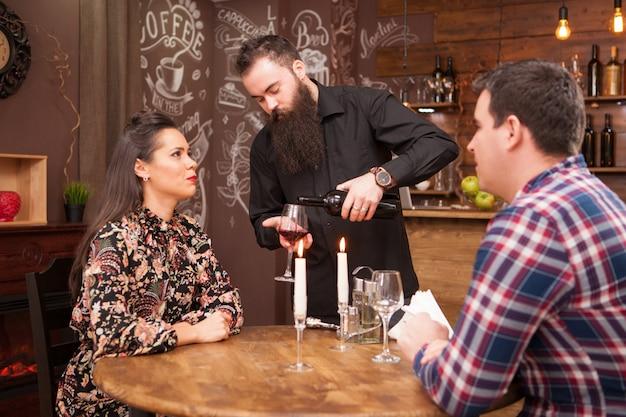 Serveur versant du vin rouge à un beau couple. bon temps.