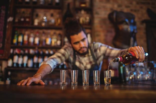 Serveur versant la tequila dans des verres à liqueur au comptoir
