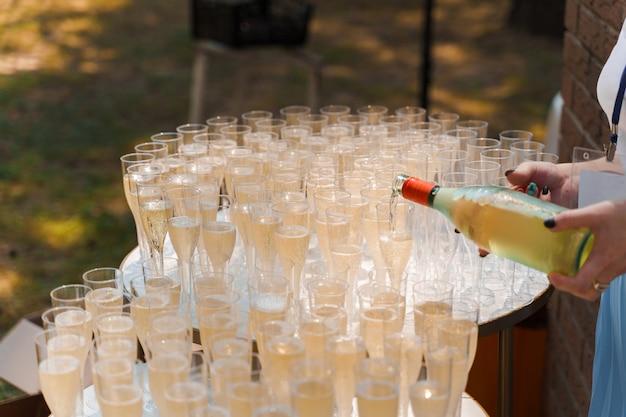 Serveur verse du champagne dans une tasse à vin en plastique jetable