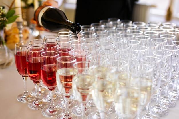 Le serveur verse du champagne dans des verres dans la rue - restauration de mariage