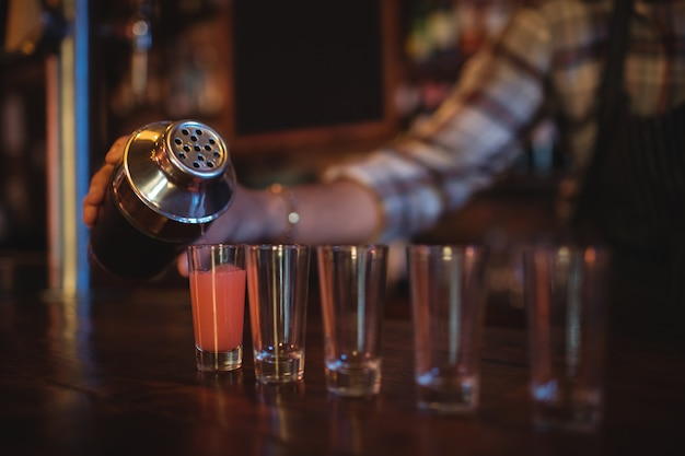 Serveur verser un cocktail dans des verres à liqueur au comptoir