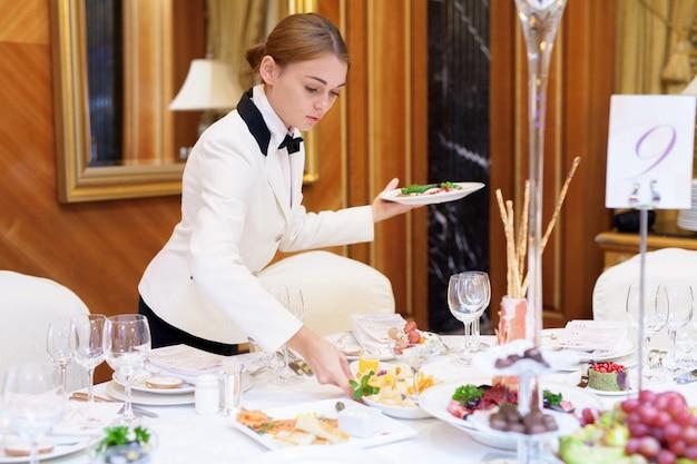 Les serveurs mettent les tables dans le restaurant pour le banquet