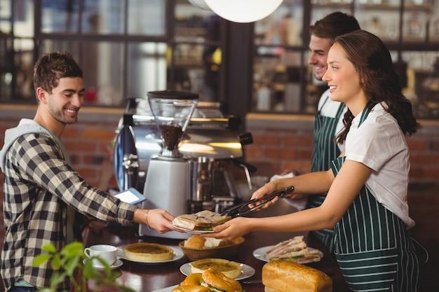 Des serveurs souriants au service d'un client