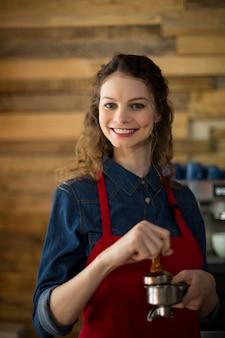 Serveuse à l'aide d'un pilon pour presser le café moulu dans un porte-filtre